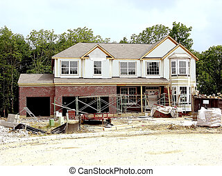 Construction - Brick Laying *** Brick laying scaffolding surrounds a house under construction on a wooded homesite in a new home community in Northern Kentucky, USA.