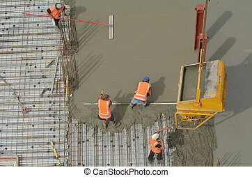Construction builders applying and leveling cement in building site