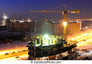 night shot of construction building site with tower cranes