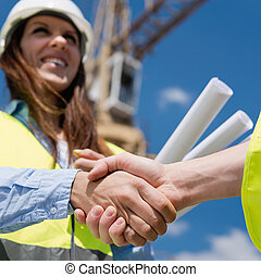 Construction business deal. Focus on handshake, architect,...