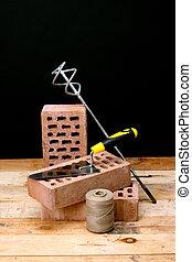 Construction concept - Bricks, trowel and stirrer on work ...