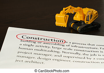 Construction concept. Paper, text and excavator
