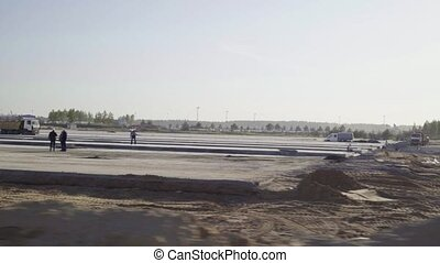 Construction, concreting of airport runways, roads. Men,...