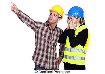 Construction couple discussing a problem
