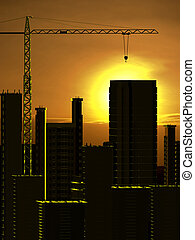 Crane and building construction on a sunset background