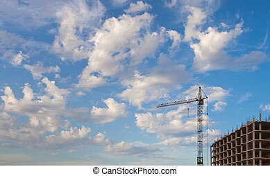 Construction crane and concrete structure against the sky