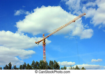 construction crane in summer against a blue sky with white clouds