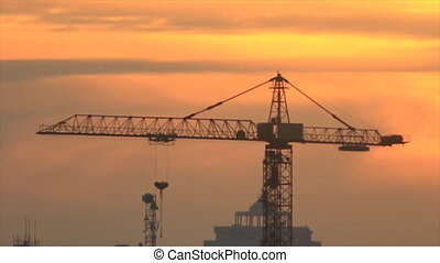 Construction crane on darkening sky - Construction crane on...