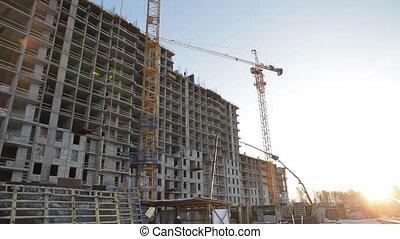 Construction crane on sunset background