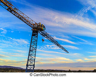 Construction crane tower on blue sky background.