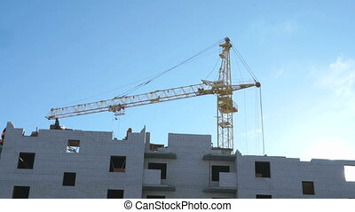 Construction crane and workers work in construction of high-rise buildings in sunny weather in winter