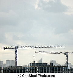 Construction cranes against the background cityscape and cloudy sky. Aerial photo from the drone.