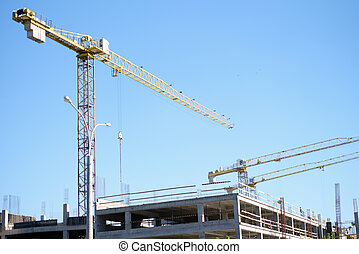 Construction cranes are standing near building houses