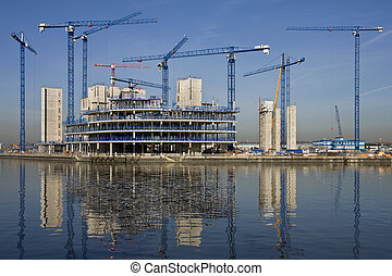 Construction cranes building a waterside office development (In Salford Quays in Greater Manchester in Great Britain)
