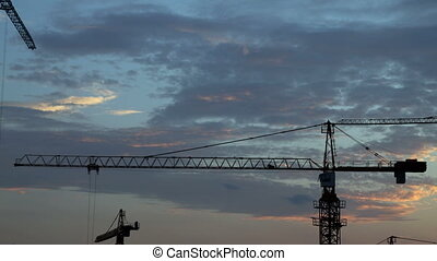 Construction cranes fading dusk into the night