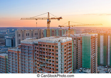 Construction cranes of high-rise residential buildings in the big city, view of the evening sky.