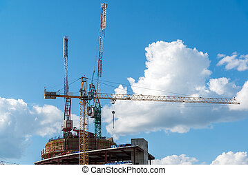 Construction cranes on background of sky with clouds