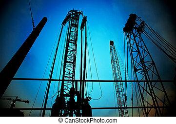 construction cranes on night ove a blue sky