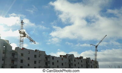Construction cranes operate on building project