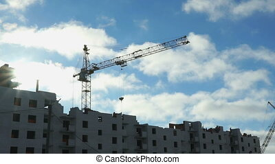 Construction cranes operate under the clouds