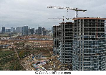 Construction cranes standing near multi storey buildings