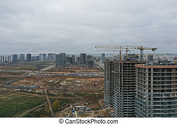 Construction cranes standing near unfinished multi storey buildings