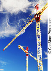 Construction cranes - Two construction cranes on blue sky ...