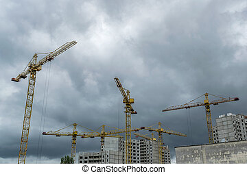 Construction cranes under the stormy sky