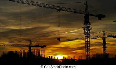 Construction Cranes - Construction cranes fading from sunset...