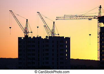Construction cranes with built houses on the background of the sunset sky