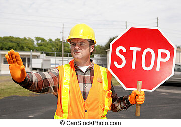 Construction Crew Stop Sign - A construction worker holding...