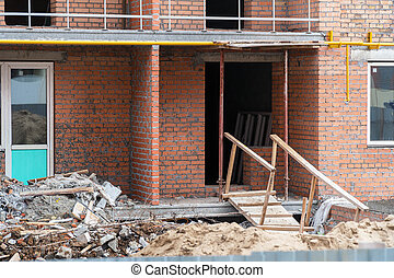 Construction debris next to a red brick house under ...