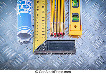 Construction drawings level wooden meter try square on grooved metal background.