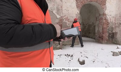 Construction engineer close up using tablet PC with worker in background