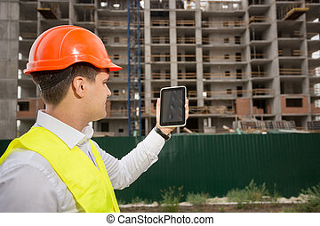 Construction engineer controlling building construction with...