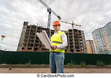 Construction engineer in hardhat on building site with working cranes