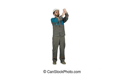 Construction engineer in helmet makes selfie on the phone  on white background.