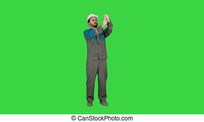 Construction engineer in helmet makes selfie on the phone  on a Green Screen, Chroma Key.