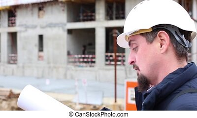 construction engineer or architect in helmet with a construction plan on the construction site.