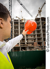Construction engineer pointing at building site with red hardhat