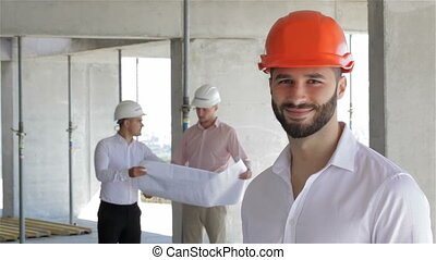 Construction engineer poses at the building under construction