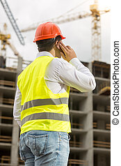 Construction engineer talking by phone and looking on...