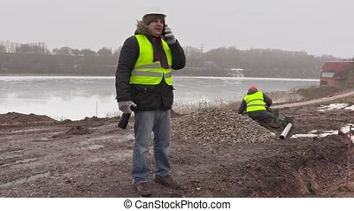 Construction engineer talking on cell phone and worker...