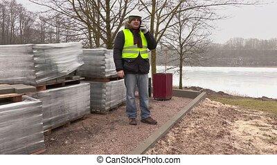 Construction engineer talking on smart phone near paving...