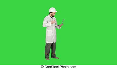 Construction engineer Videoconferencing With laptop on a Green Screen, Chroma Key.