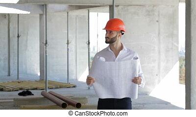 Construction engineer walks through the building under construction