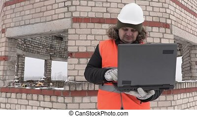 Construction engineer with laptop give directions to the...