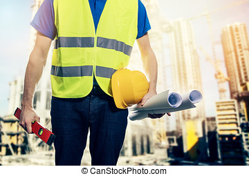 construction engineer with safety vest and blueprint rolls...