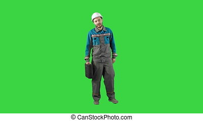 Construction engineer with tablet and drawing in hands, man walks at camera on a Green Screen, Chroma Key.