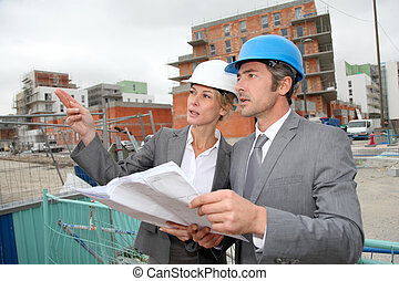 Construction engineers checking plan on building site